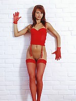 Sexy redhead with oiled body posing in a gloves and red fishnets